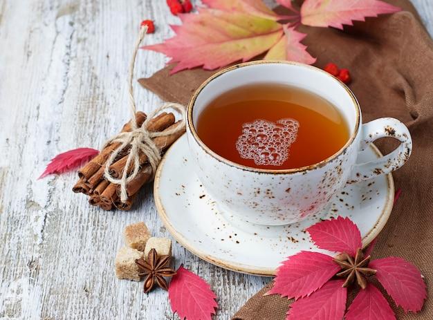 Tazza di tè di autunno su fondo in legno chiaro