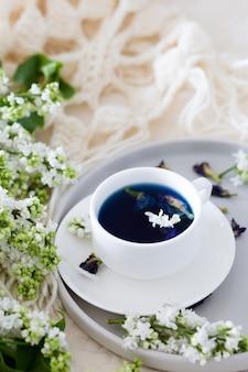 Tazza di tè di piselli di farfalla (fiori di pisello, pisello blu) per bere sano, bere disintossicante e lillà bianco.