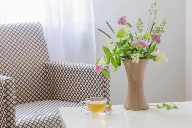 Tazza di tè e bouquet estivo in vaso al coperto