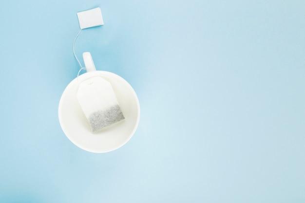 Tazza di tè e bustine di tè su sfondo blu.