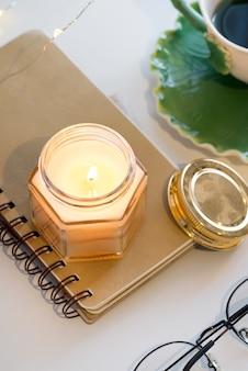 Tazza di tè e candele aromatiche su un taccuino su una tavola bianca