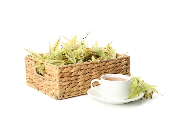 Tazza di tè e cestino di vimini con il tiglio isolato su bianco