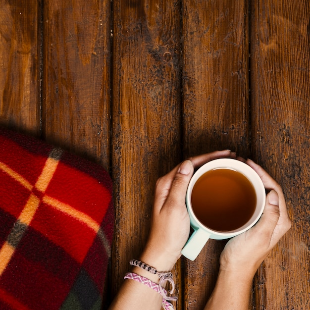 Tazza di tè e coperta invernale su legno vecchio