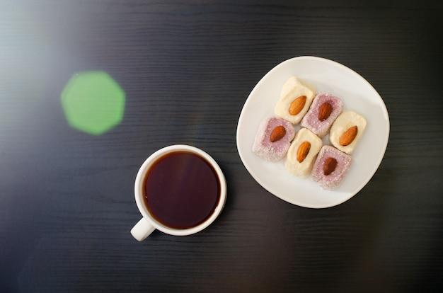 Tazza di tè e delizia turca con mandorle su un piattino, brillamento solare, vista dall'alto