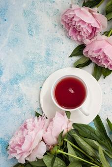 Tazza di tè e fiori di peonie rosa