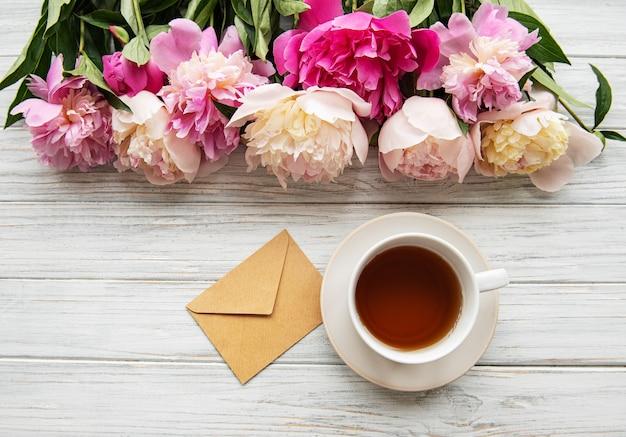 Tazza di tè e peonie rosa