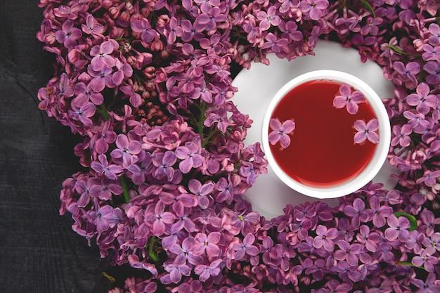 Tazza di tè e rami del lillà di fioritura del mazzo dei fiori della molla sulla tavola nera progettazione creativa dei fiori disposizione piana. posto per il testo.