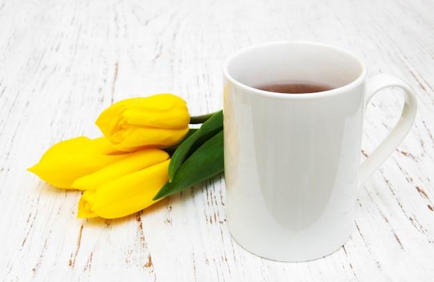 Tazza di tè e tulipani gialli