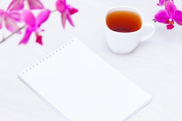 Tazza di tè, fiori, quaderno di carta. copywriting, concetto freelance.