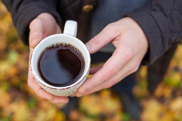 Tazza di tè in mano all'aperto. passeggiata nella foresta d'autunno.
