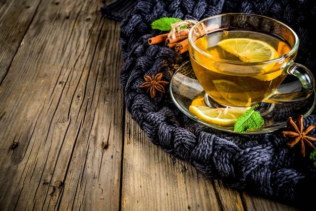 Tazza di tè in vetro con limone, menta e spezie, sul vecchio tavolo di legno rustico con coperte calde.