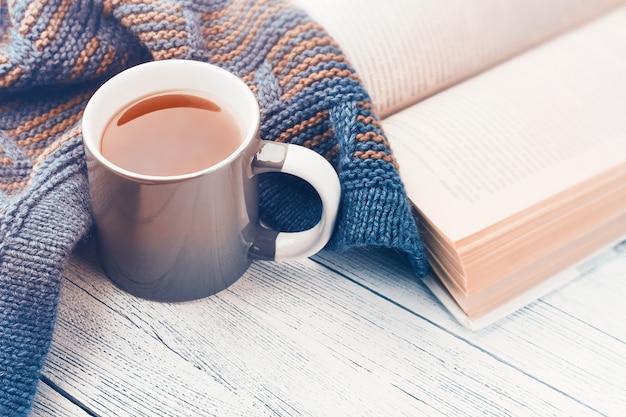 Tazza di tè, libro e sciarpa lavorata a maglia su legno