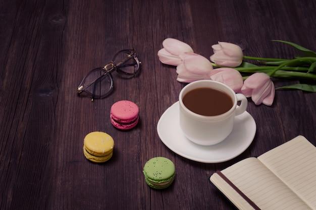 Tazza di tè, macarons, bicchieri, tulipani rosa