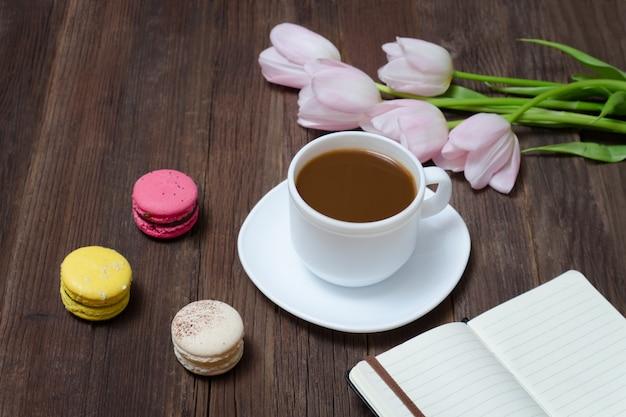 Tazza di tè, macarons, tulipani rosa e taccuino