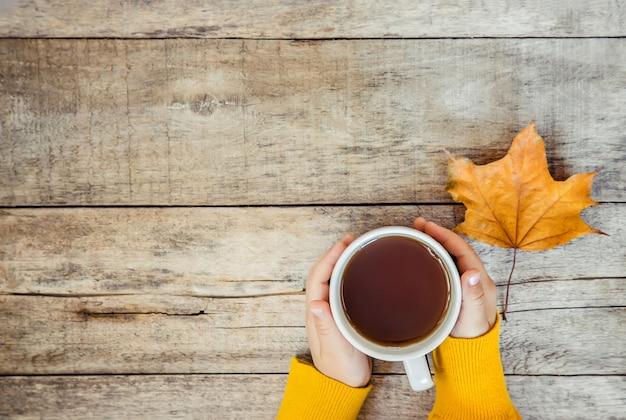 Tazza di tè nelle mani di un bambino e un accogliente autunno sfondo. messa a fuoco selettiva