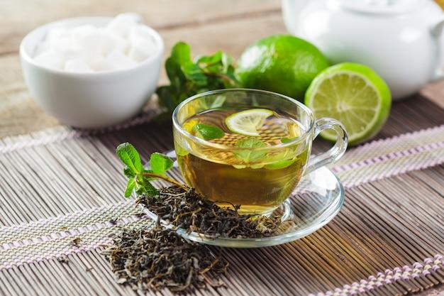 Tazza di tè nero con foglie di menta su un tavolo di legno