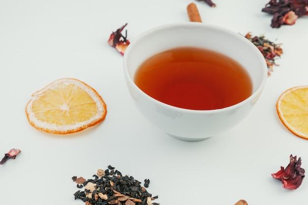 Tazza di tè nero e foglie su sfondo bianco