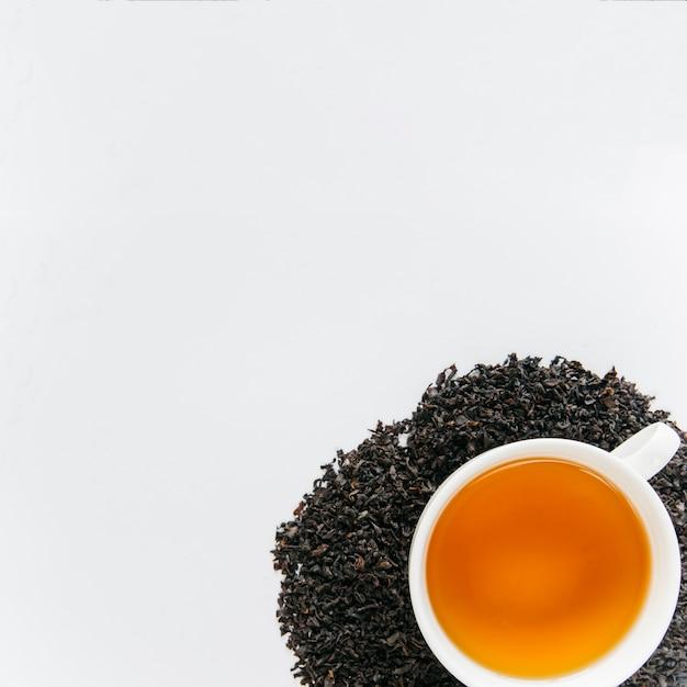 Tazza di tè nero sopra le foglie secche nere isolate su sfondo bianco