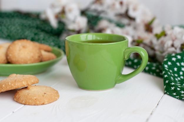 Tazza di tè nero su un tovagliolo verde, biscotti fatti in casa, un ramo di fioritura di albicocca