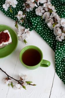 Tazza di tè nero su un tovagliolo verde, pane di segale fatto in casa con crema di formaggio morbido e pomodori secchi affumicati, un ramo di fioritura di albicocca