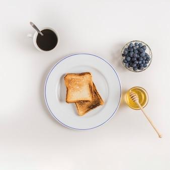 Tazza di tè; pane tostato; ciotola di miele e mirtilli su sfondo bianco