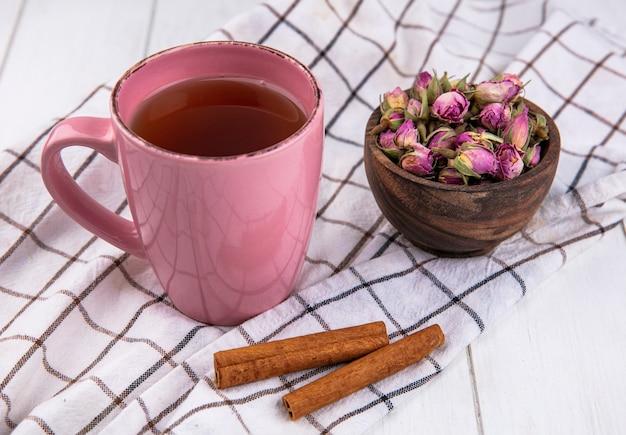 Tazza di tè rosa vista laterale con cannella e fiori secchi su un asciugamano bianco a scacchi