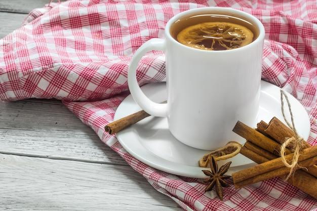 Tazza di tè su una tovaglia rossa, bellissimo sfondo bianco in legno, bastoncini di cannella, limone e frutti di bosco