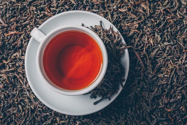 Tazza di tè su uno sfondo di erbe di tè. vista dall'alto.