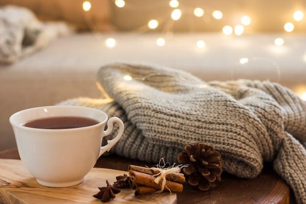 Tazza di tè sul tappetino in legno con plaid lavorato a maglia