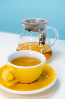 Tazza di tè sulla tavola bianca e sulla parete blu