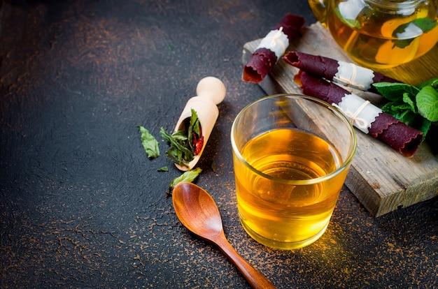 Tazza di tè, tè in un cucchiaio e frutta secca