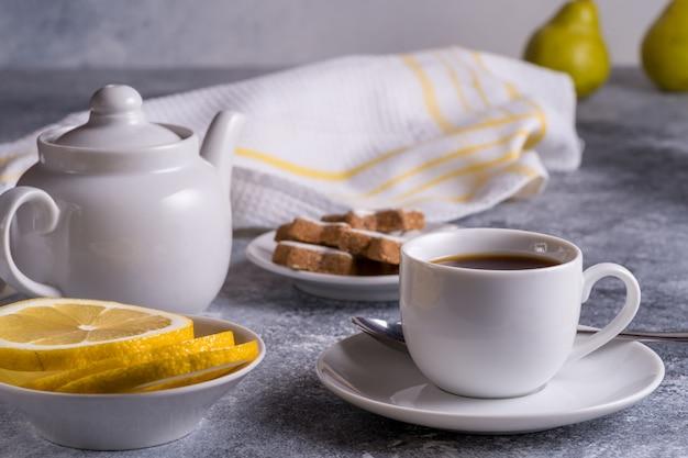 Tazza di tè, teiera, torte e limone su un tavolo