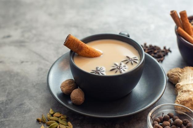 Tazza di tè tradizionale masala chai indiano con ingredienti: cannella, cardamomo, anice, noce moscata
