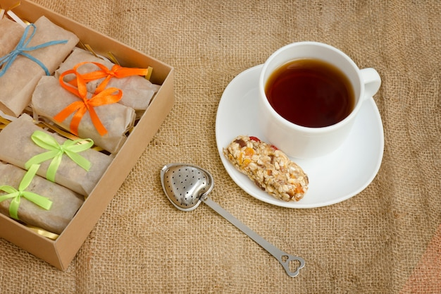 Tazza di tè, un bar di muesli e scatole di bar. tela di sacco