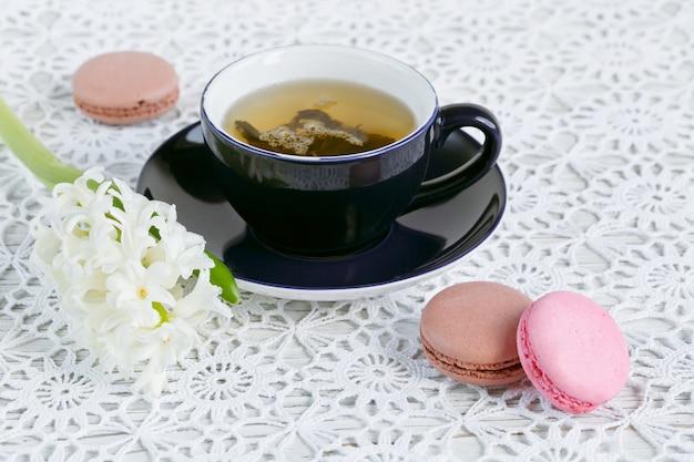 Tazza di tè verde, amaretto di colore e fiori bianchi