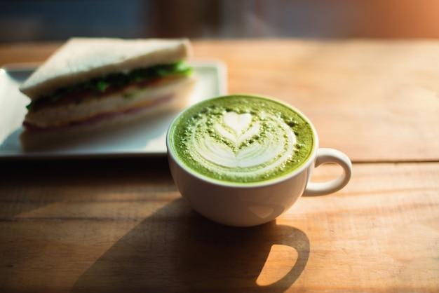Tazza di tè verde con motivo a cuore in una tazza bianca e sandwich sul fondo della tavola in legno