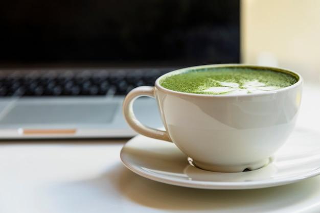 Tazza di tè verde giapponese tradizionale di matcha vicino al computer portatile sullo scrittorio