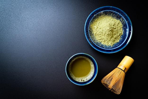 Tazza di tè verde matcha calda con polvere di tè verde e frusta