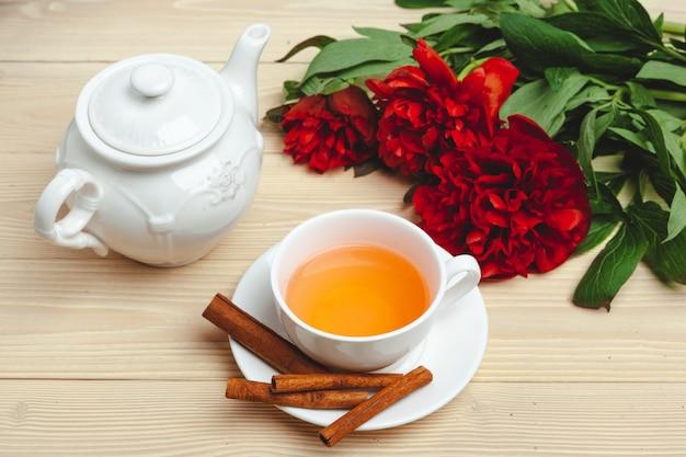 Tazza di tè verde sul tavolo con fiori di peonia freschi