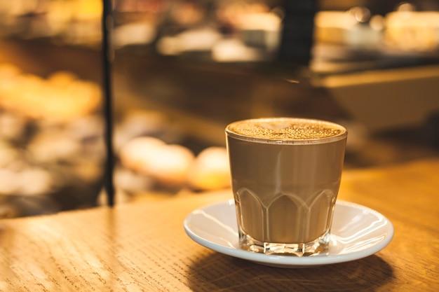 Tazza di vetro delizioso gustoso latte con piattino sul tavolo
