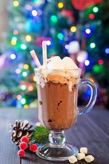 Tazza di vetro di cioccolata calda con mini marshmallows con rami di pino uno sfondo rustico