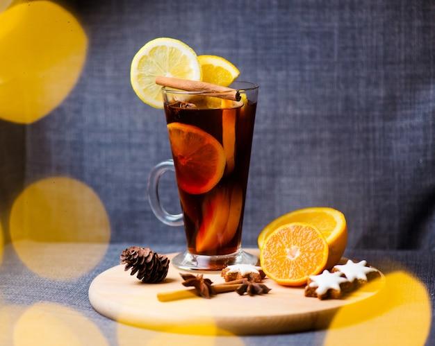 Tazza di vetro di spezie vin brulé rosse calde, biscotti di pasta frolla con zucchero a forma di stella, anice e polvere di cannella in vassoio di argilla con tela di sacco su legno scuro
