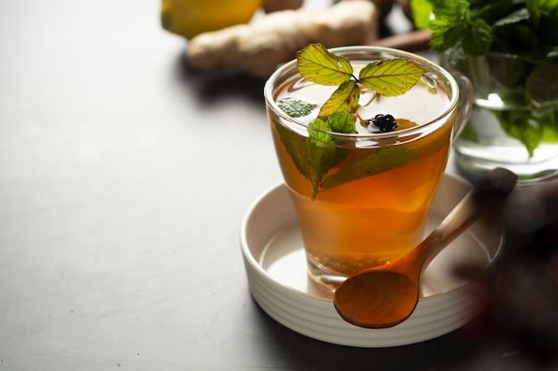 Tazza di vetro di tè allo zenzero con limoni e foglie di menta su superficie scura,