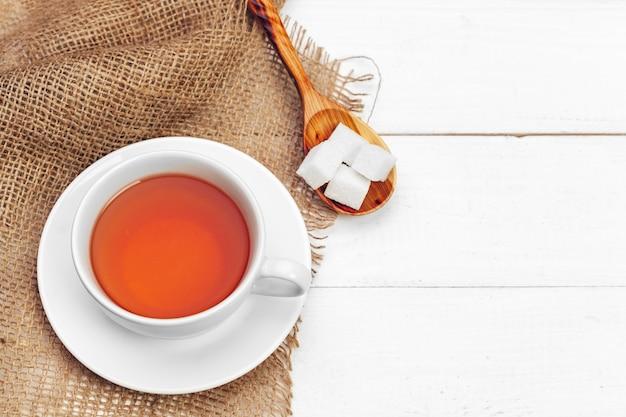 Tazza di vetro di tè caldo con zucchero sul tavolo