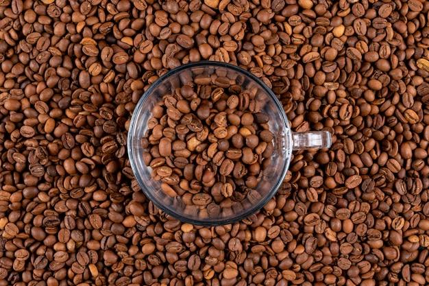 Tazza di vetro di vista superiore sulla superficie dei chicchi di caffè