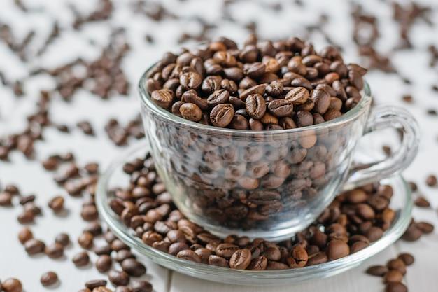 Tazza di vetro e piattino traboccante di un sacco di chicchi di caffè su un tavolo di legno bianco. cereali per la preparazione della bevanda popolare.