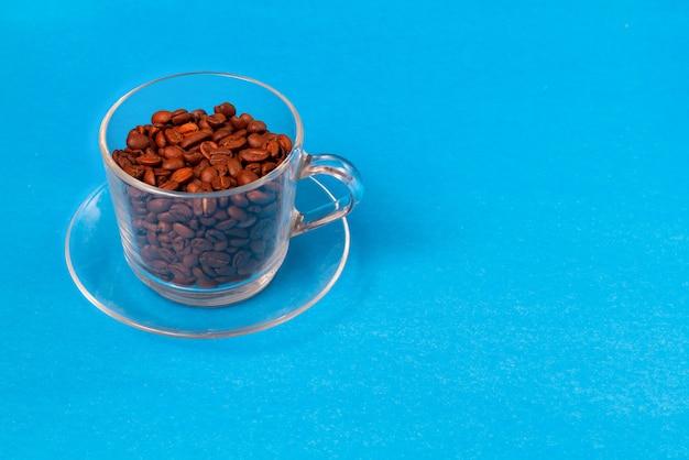 Tazza di vetro trasparente con chicchi di caffè con fette di zucchero greggio su sfondo blu. copia spazio.