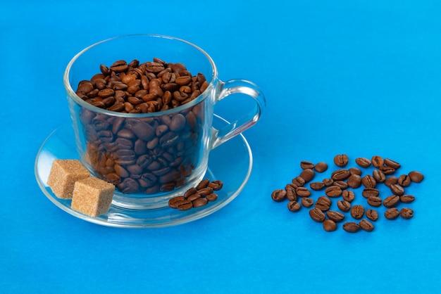 Tazza di vetro trasparente con chicchi di caffè con fette di zucchero grezzo cosparsi di chicchi di caffè sul blu