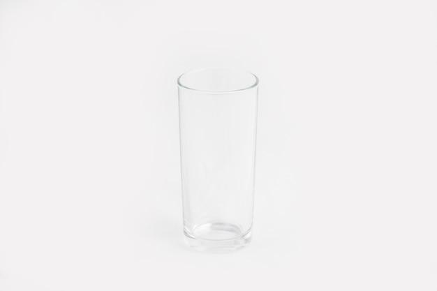 Tazza di vetro trasparente elegante isolata su una parete bianca