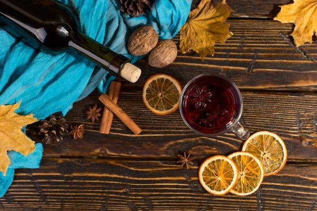 Tazza di vin brulè con spezie, bottiglia, sciarpa, foglie secche e arance su un tavolo di legno. mood autunnale, metodo per scaldarsi al freddo, copyspace.